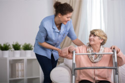 caregiver assisting the senior woman to stand